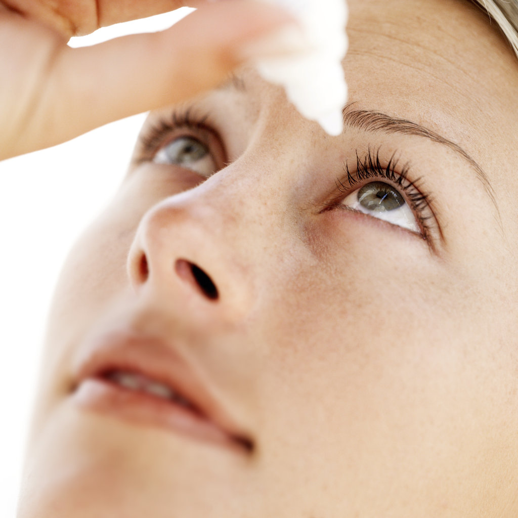 woman with dry eyes applying eye drops